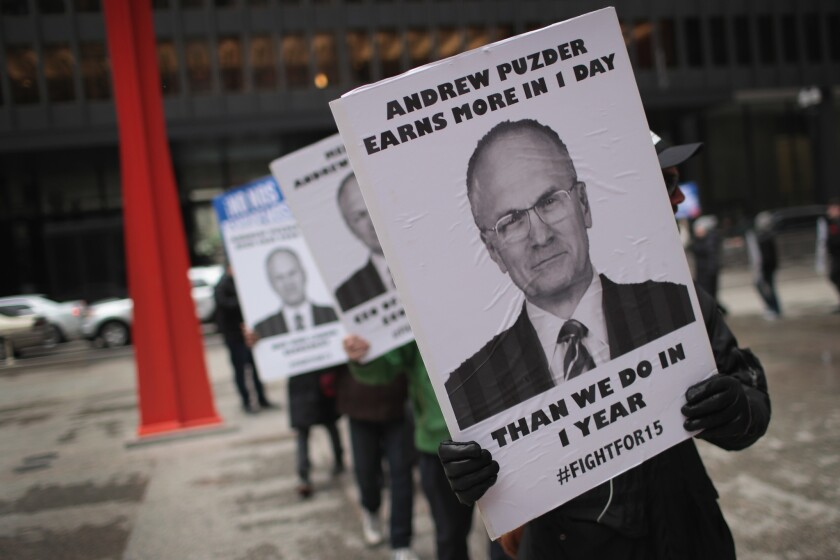 Fight for $15 workers in Chicago protest the nomination of Andy Puzder for Labor secretary.
