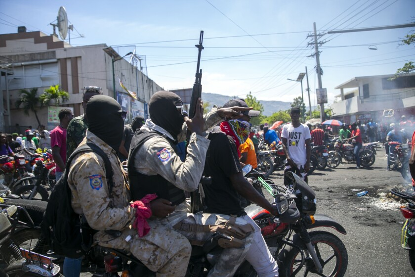 Armed and masked police officers move forward on a motorcycle during a protest in  Haiti