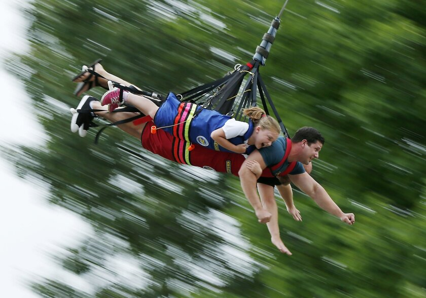FILE - In this July 14, 2016 file photo, Lilly Caron, of Bridgeton, Maine, Jason Homchick, of San Diego, and Lilly's father Jason Caron, (obscured), ride the Sky Swing at Seacoast Adventure outdoor summer attractions park in Wyndham, Maine. Some protectors of Maine's image as a vacation destination