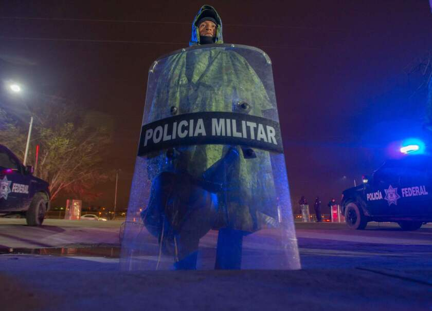 A Mexican military police officer guards a warehouse used as a shelter for Central American migrants in Piedras Negras, Coahuila state, at the U.S. border.