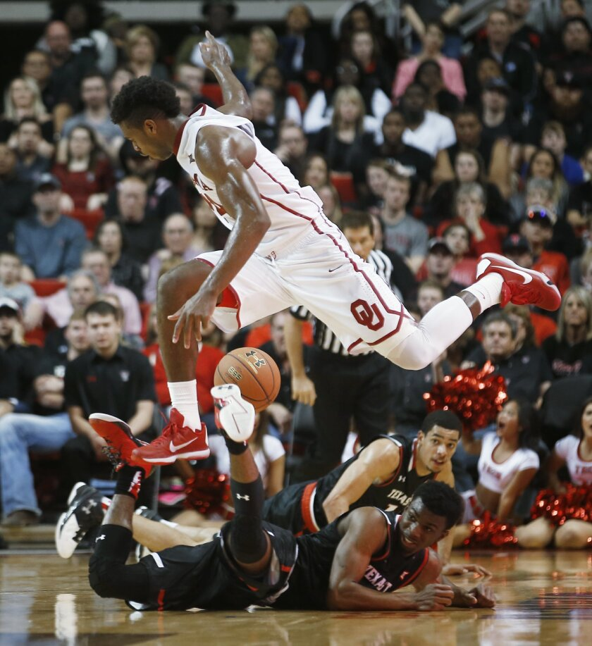 Oklahoma's Buddy Hield jumps over two Texas Tech players during an NCAA college basketball game Wednesday, Feb. 17, 2016, in Lubbock, Texas. Texas Tech won 65-63. (AP Photo/Brad Tollefson)