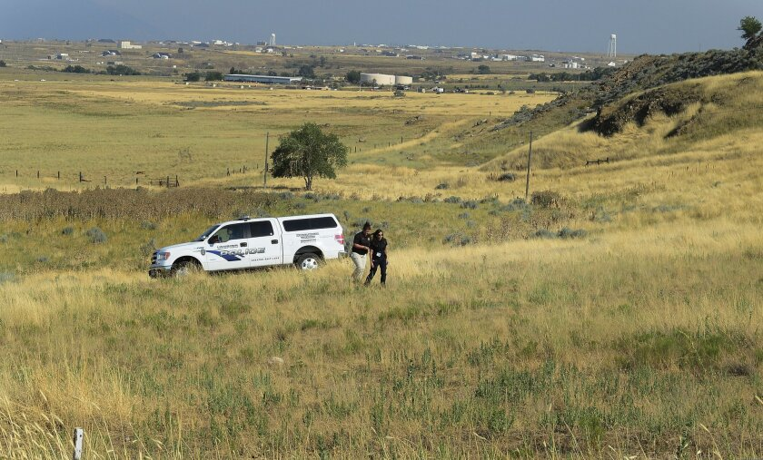 Unified police search a field in Magna, Utah, where at least nine horse were found to be abandoned without water, Friday, July 18, 2014. Many of them died before help could reach them. (AP Photo/The Salt Lake Tribune, Scott Sommerdorf)