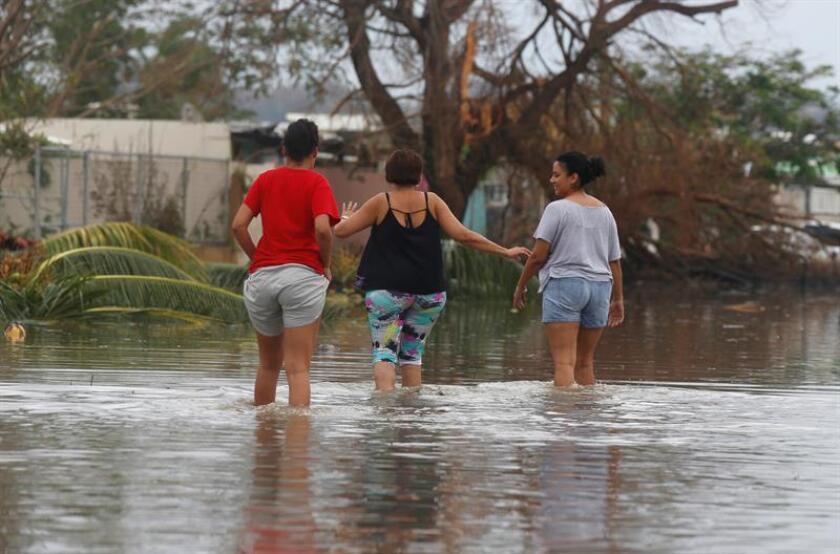 Unas mujeres cruzan una calle inundada tras el paso del huracán María en la municipalidad de Toa Baja (Puerto Rico). EFE/Archivo