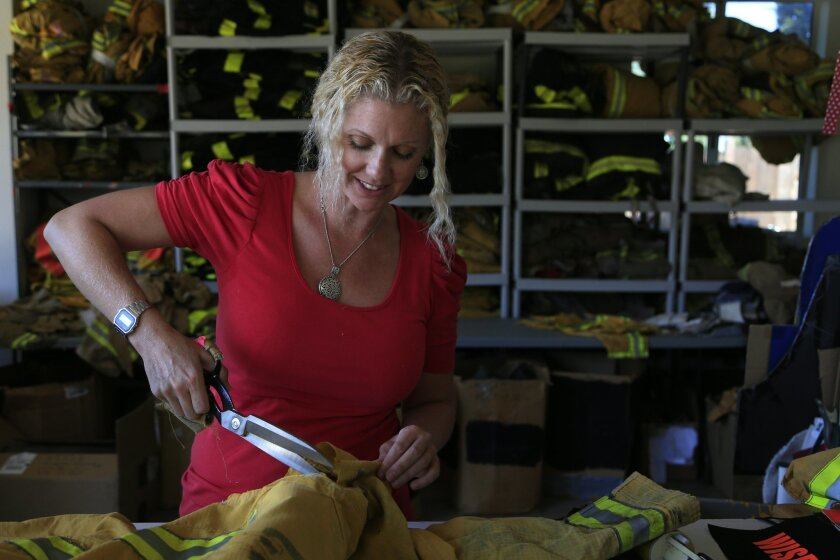 Niki Rasor dismantles an expired fireman's coat and pants to create unique purses and carry-alls out of her Vista garage.