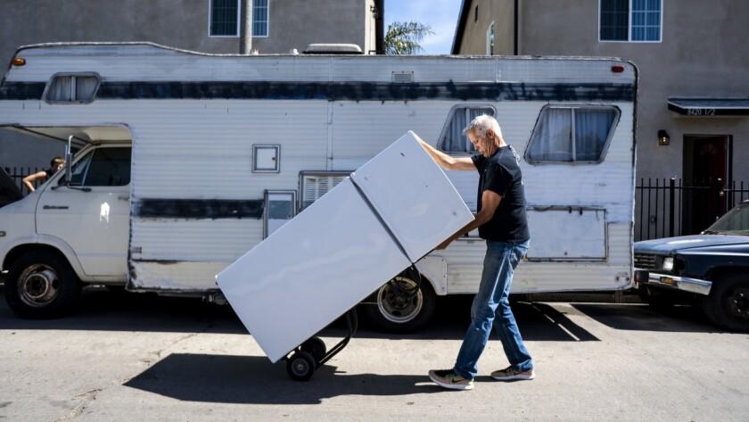 LOS ANGELES, CA - MARCH 06: John Betz rolls a refrigerator down Wall street as he and Heidi Roberts
