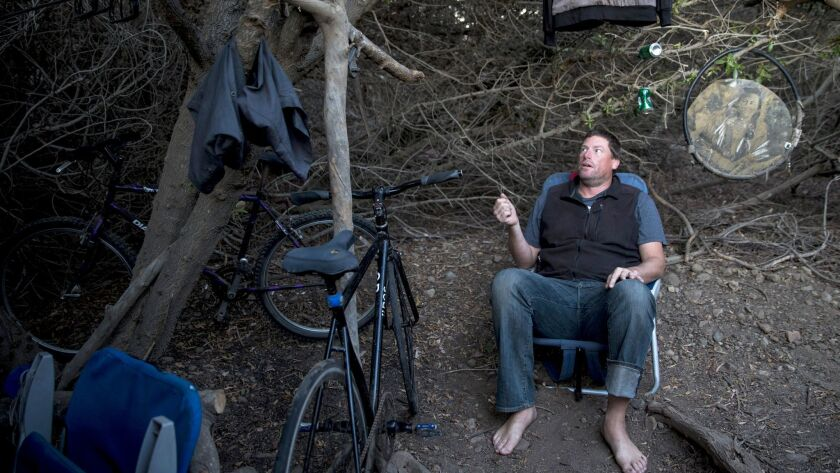 MALIBU, CA - NOVEMBER 15: Chris Smith sits in a chair next to his tent at a homeless camp in the bus