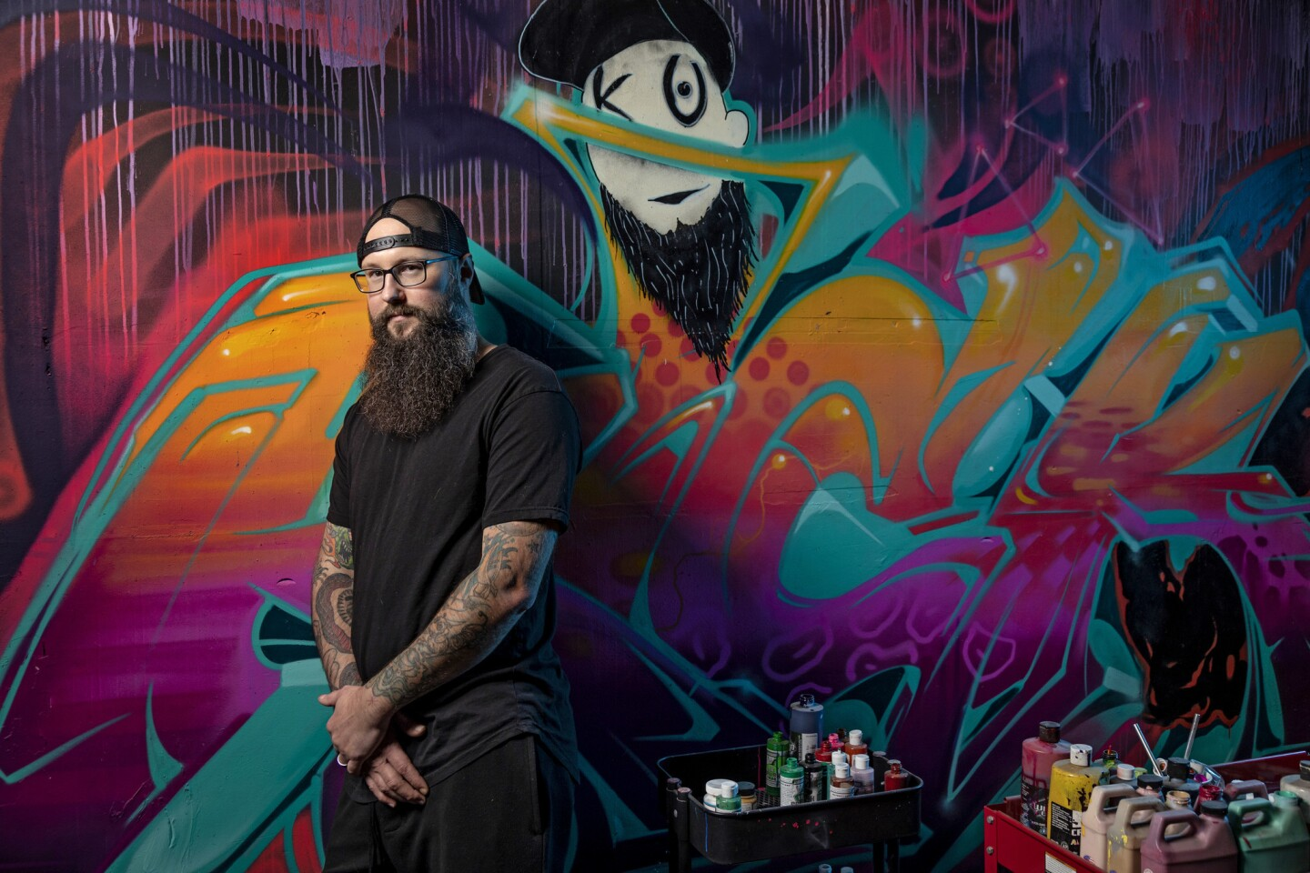 Troy Cole, a.k.a. Kickasso, in front of a mural by artist Jonathan Cirlin, a.k.a. Espy Dpt/Znc, at his workshop, Kickasso Kustoms, in downtown Los Angeles.