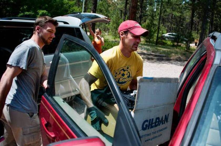 Brothers Patrick, left, and Sean Collins load a car with belongings as they and their family prepare to evacuate from their home in the Colorado Springs area. Evacuation orders have been given to 39,000 people as the Black Forest fire continues to spread.