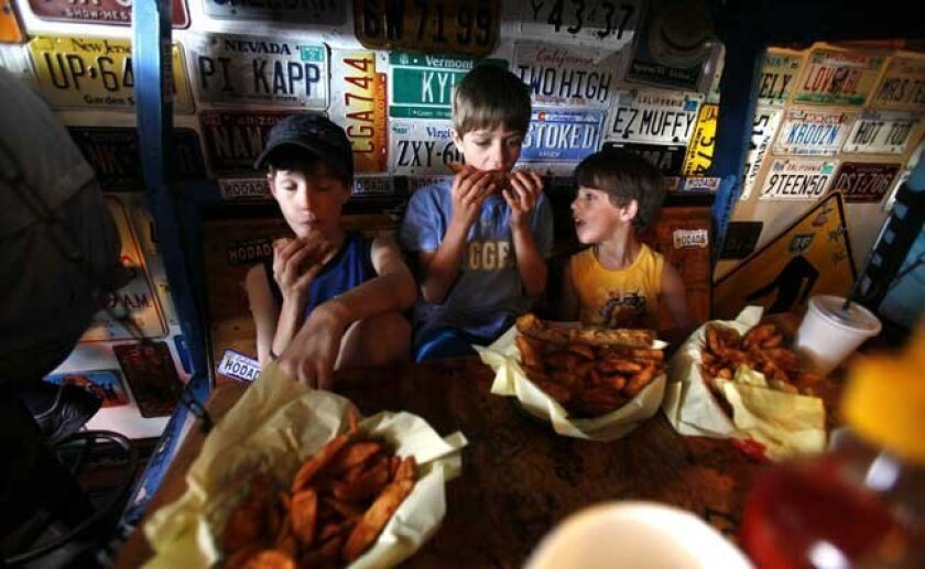 Opting for grilled cheese sandwiches instead of burgers, three brothers Bryce Shutto, 10, left, Cameron, 8 and Dominic, 5, relax in the converted car table at Hodad's, OB.