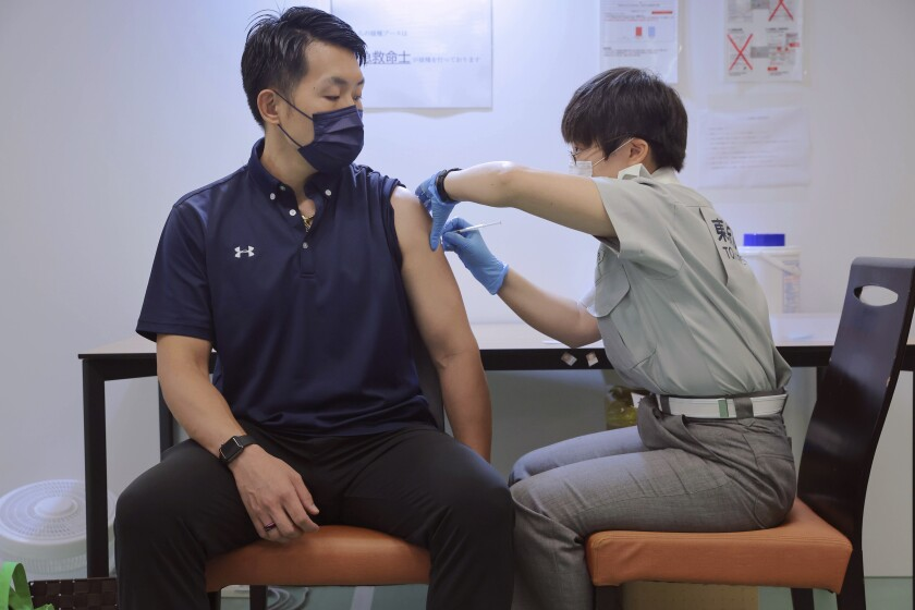 FILE - In this Aug. 2, 2021, file photo, a visitor receives a shot of the Pfizer COVID-19 vaccine at the Tokyo Vaccination Center at Aoyama Gakuin University in Tokyo. In a new government policy that was debated in parliament on Wednesday, Aug. 4, 2021, coronavirus patients with moderate symptoms will isolate at home instead of in hospitals, as new cases surge in Tokyo to record levels during the Olympic Games. (Stanislav Kogiku/Pool Photo via AP)