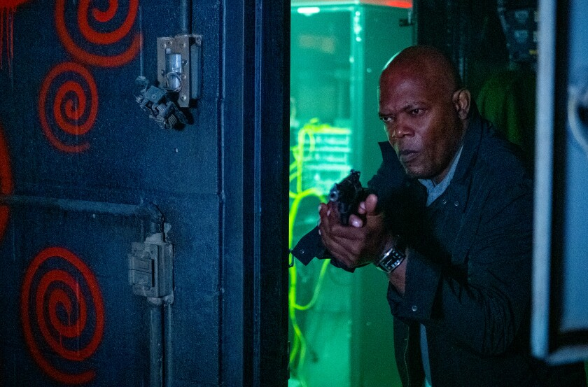 Samuel L. Jackson aims a gun into a room painted with spirals.