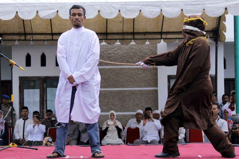 An Islamic Shariah law official whips a man, convicted of gambling, with a rattan cane watched by people inside a mosque compound in Banda Aceh, Aceh Province, Indonesia, Friday, Oct 3, 2014. Indonesian authorities publicly caned four men who were convicted of gambling in conservative Aceh province after Friday prayers. (AP Photo/Heri Juanda)
