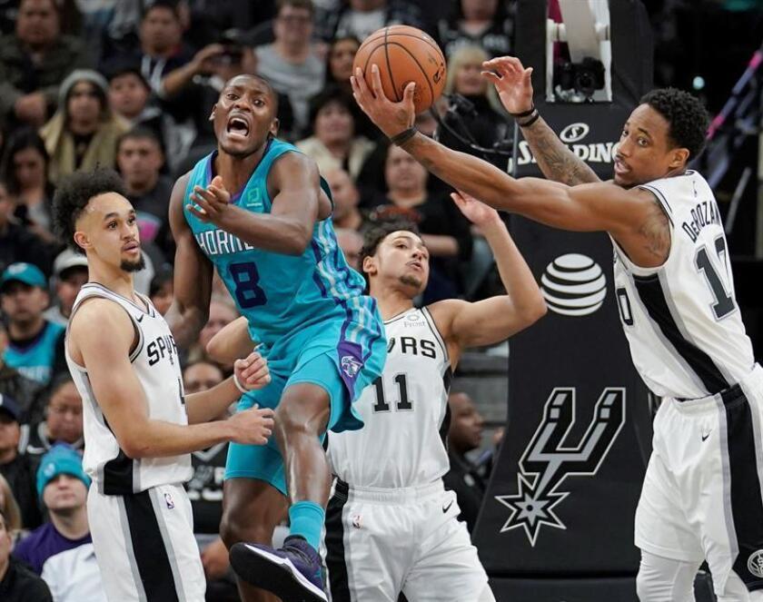 DeMar DeRozan (d) de San Antonio Spurs en acción ante Bismack Biyombo (8) de Charlotte Hornets durante un partido de baloncesto de la NBA entre San Antonio Spurs y Charlotte Hornets disputado hoy en el AT&T Center de San Antonio, Texas (EE.UU.). EFE