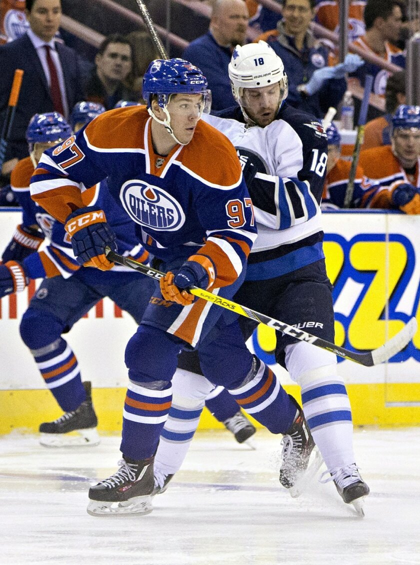 Winnipeg Jets' Bryan Little (18) and Edmonton Oilers' Connor McDavid (97) vie for the puck during the first period of an NHL hockey game Saturday, Feb. 13, 2016, in Edmonton, Alberta. (Jason Franson/The Canadian Press via AP)