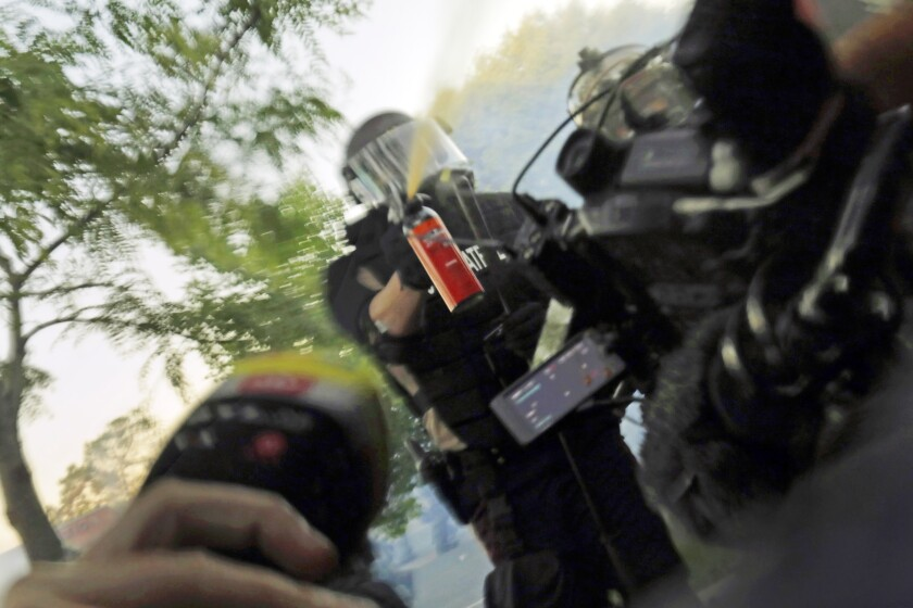 A journalist's equipment is in the foreground as a trooper in riot gear shoots pepper spray toward the camera.