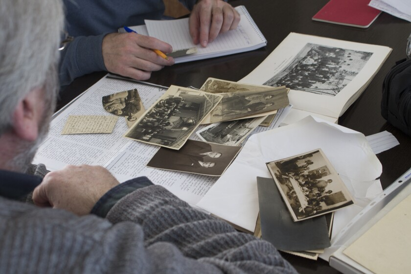 Vahé Tachjian takes notes and examines family photos