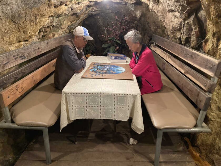 A couple sits at a booth inside a mine, working a puzzle