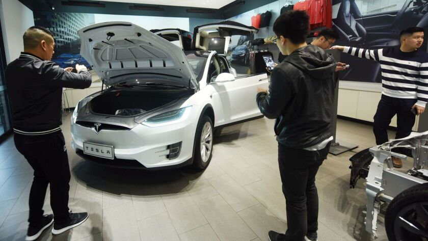 People look at Tesla cars at a showroom in Hangzhou, China.