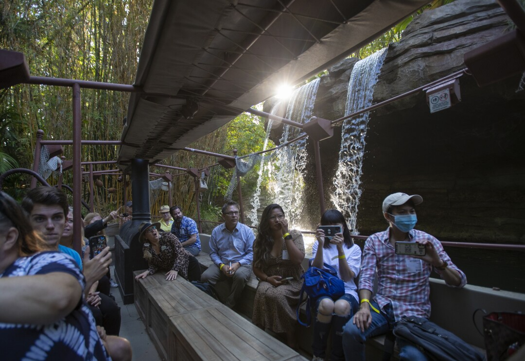 Riders on benches on the Jungle Cruise ride pass in front of the Schweitzer Falls