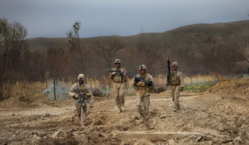 Marines walk just outside Patrol Base Fires in what they call the picket line. The line is where Marines position themselves with armored vehicles as a defensive measure for the patrol base.
