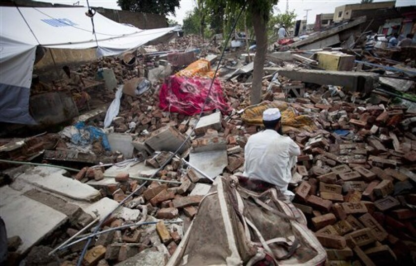 A flood-affected man sits over debris of his house collapsed by flooding in Nowshera, northwest Pakistan, Monday, Aug. 9, 2010. The number of people suffering from the massive floods in Pakistan exceeds 13 million, more than the combined total of the 2004 Indian Ocean tsunami, the 2005 Kashmir eart