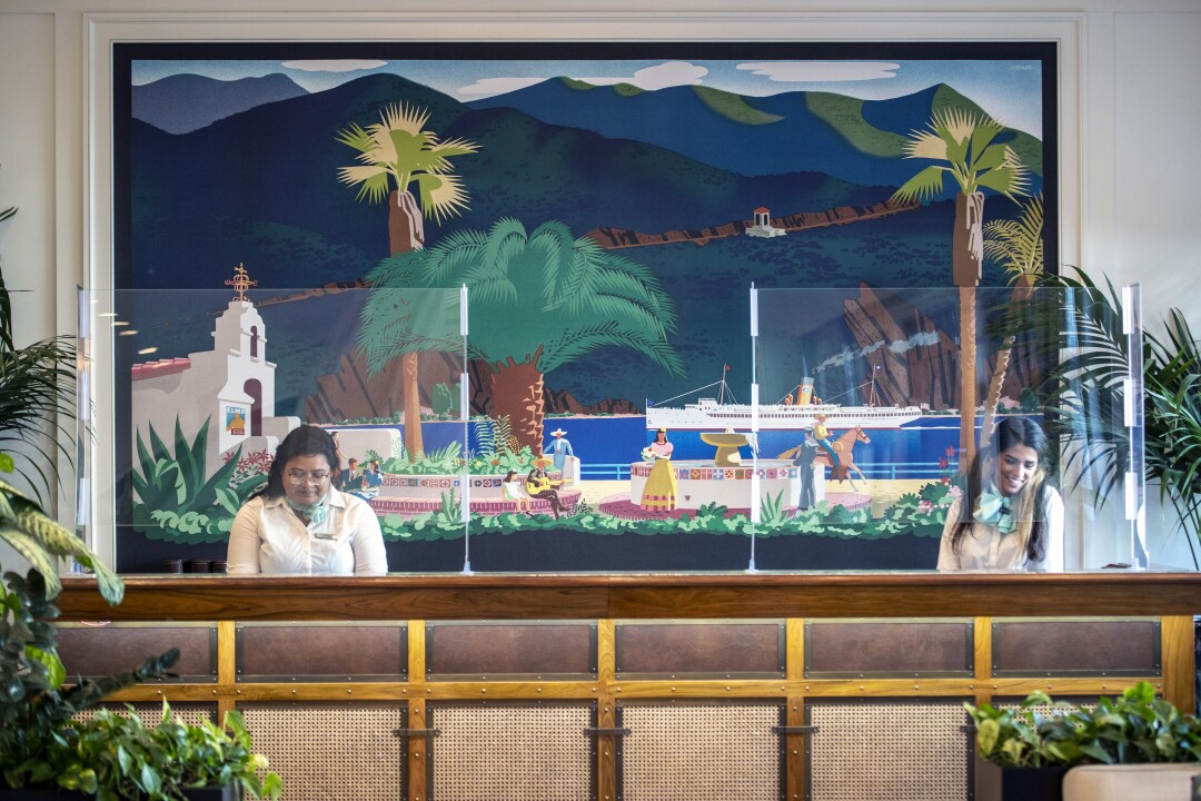 A hotel front counter backed by a mural of palm trees, ocean, a cruise ship and a Spanish Revival-style building