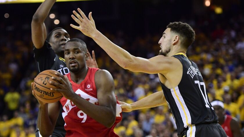Toronto Raptors center Serge Ibaka (9) holds the ball as Golden State Warriors guard Klay Thompson,