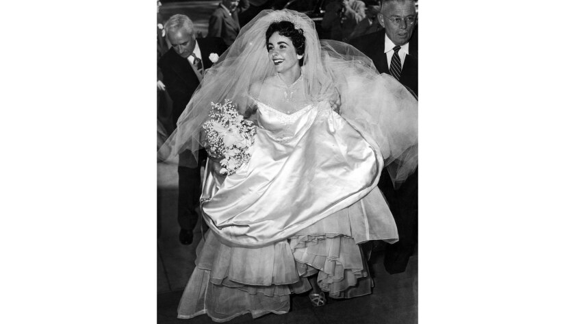 """May 6, 1950: Gathering up her gown, Elizabeth Taylor enters the Church of the Good Shepherd in Beverly Hills for her marriage to Conrad """"Nick"""" Hilton Jr."""