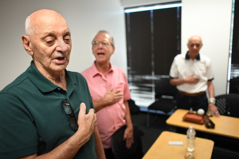 Al Hassan sings along during the national anthem at the start of BasebALZ's July meeting.