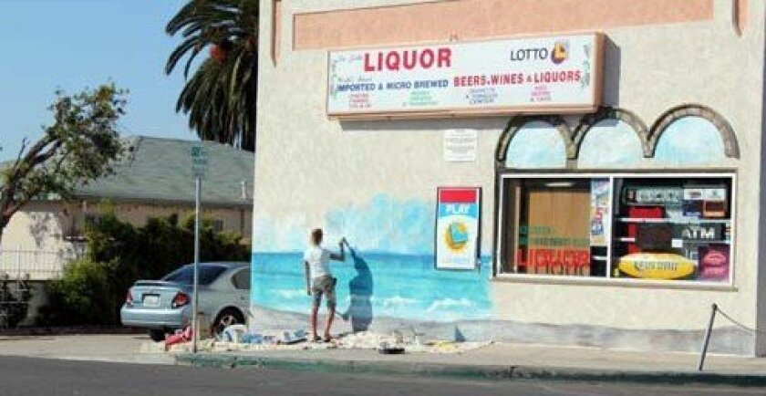 An artists works on a seascape on the side of La Jolla Liquor. Photo: Dave Schwab