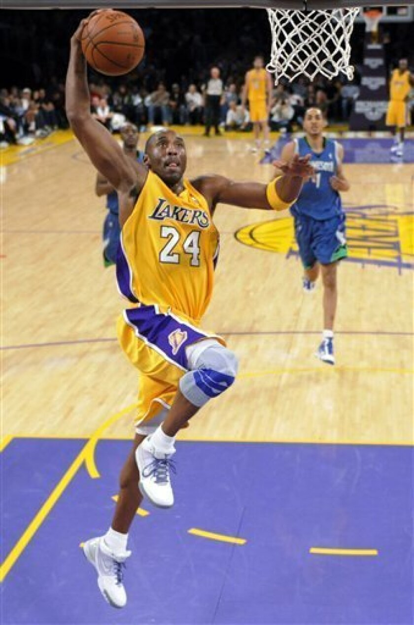 Los Angeles Lakers guard Kobe Bryant goes up to dunk the ball as Minnesota Timberwolves center Ryan Hollins gives chase during the first half of their NBA basketball game, Friday, Dec. 11, 2009, in Los Angeles. (AP Photo/Mark J. Terrill)