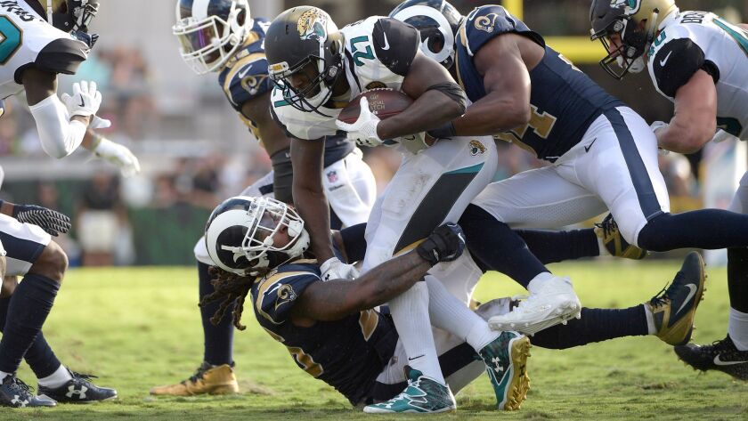 Jacksonville Jaguars running back Leonard Fournette (27) is tackled by Los Angeles Rams linebacker Mark Barron (26) and outside linebacker Robert Quinn (94).