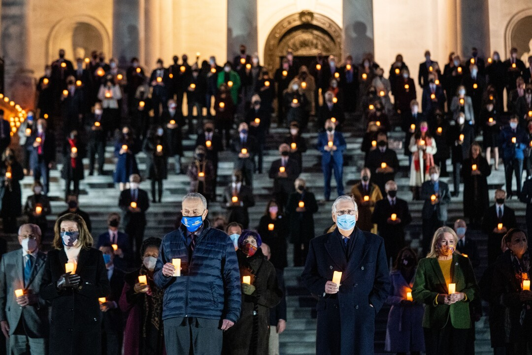 Members of the 117th Congress hold candles in a moment of silence
