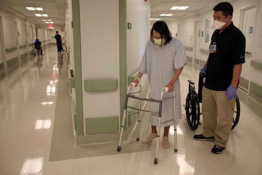 Matthew Kennedy, 39, left, of Venice works with Physical Therapy Supervisor Ralph Lingad, right, at the inpatient Tuberculosis Unit Olive View–UCLA Medical Center in Sylmar on Aug. 13, 2012. The unit is a state–of–the art ward for highly infectious patients.