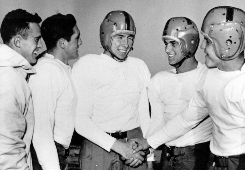 FILE - In this Dec. 11, 1953, file photo, Notre Dame player John Lattner, center, winner of the 1953 Heisman tropy and second-time winner of the Maxwell trophy, receives congratulations from teammates at practice in South Bend, Ind. Lattner, who helped lead Notre Dame to a 9-0-1 record and a No. 2