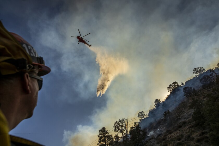 A firefighter watches as a helicopter drops water on the Bobcat fire in Llano, Calif., on Sept. 20.