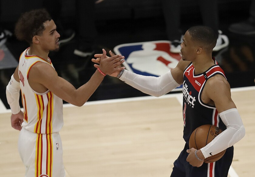Washington Wizards' Russell Westbrook, right, is congratulated by Atlanta Hawks' Trae Young after an NBA basketball game Monday, May 10, 2021, in Atlanta. Westbrook recorded his 182nd career triple-double, passing Oscar Robertson for the most in NBA history. (AP Photo/Ben Margot)