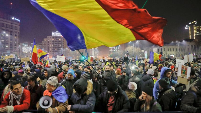 A man waves a large Romanian flag in Bucharest, Romania, on Thursday during a protest by tens of thousands against a government decree that dilutes what qualifies as corruption.
