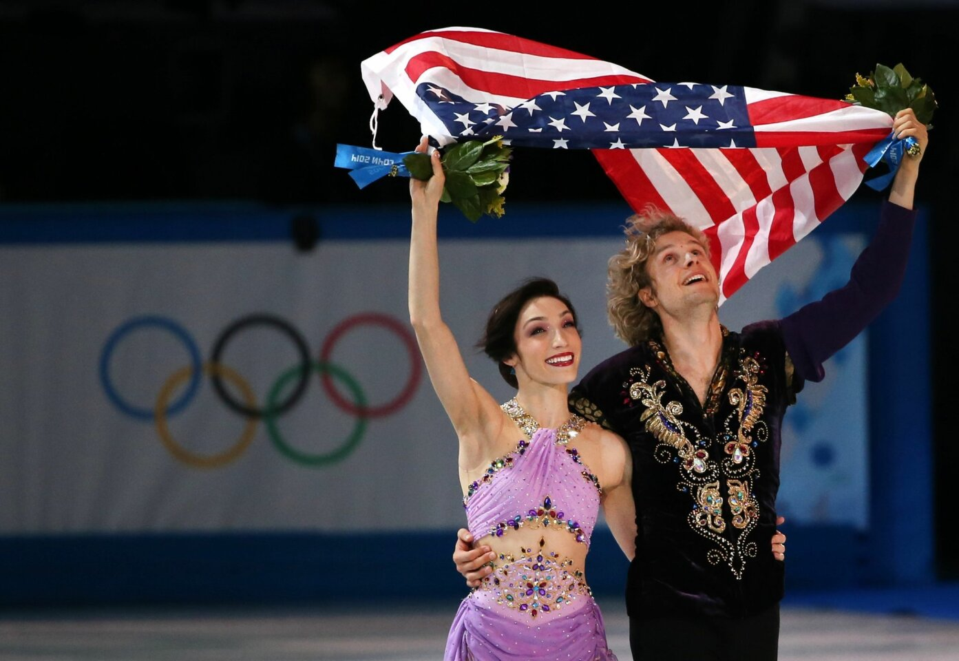 Taking a victory lap, Meryl Davis and Charlie White wave to the audience after winning Gold.