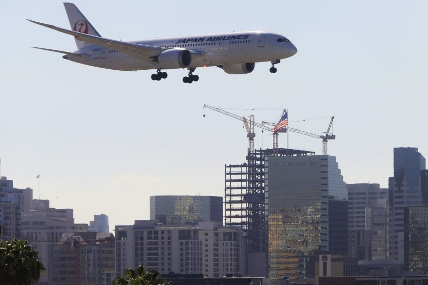 Planes make their approach to Lindbergh Field about 1/2 to 3/4 of a mile from cranes at the construction site of the new Superior Court building, seen in the background, on Wednesday in San Diego, CA. PLEASE NOTE: that the plane is not flying over the building. The two objects are more than 1/2 mile apart.)