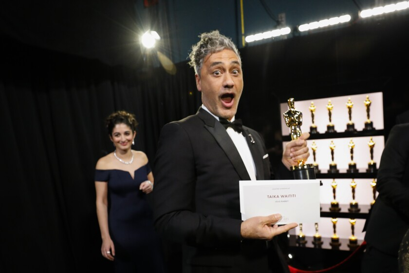 "Taika Waititi clutches his adapted screenplay Oscar for ""Jojo Rabbit."""