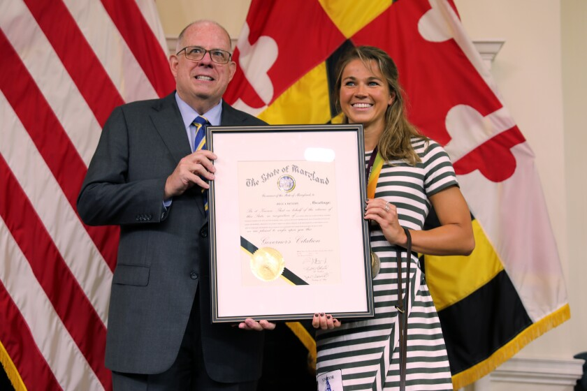 """Maryland Gov. Larry Hogan, left, presents a citation to Becca Meyers on Monday, July 26, 2021 in Annapolis, Md., recognizing her """"bravery for highlighting the issue of inequality and access for people with disabilities."""" Meyers, a Maryland native who is deaf and blind and won three gold medals in the last Paralympics, withdrew from the Tokyo games because she could not bring her mother with her as her personal care assistant. (AP Photo/Brian Witte)"""