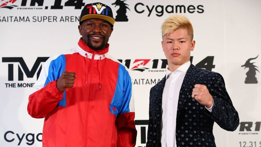 This handout photograph taken by Rizin Fighting Federation shows Floyd Mayweather Jr. (L) posing with his opponent, Japanese kickboxer Tenshin Nasukawa (R) during a press conference.