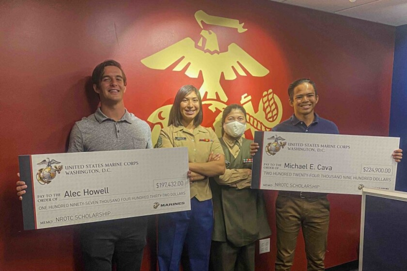 USMC Staff Sgt. Maria Arzate and Capt. Katie Sliwoski present Alec Howell and Michael Cava with their scholarships.