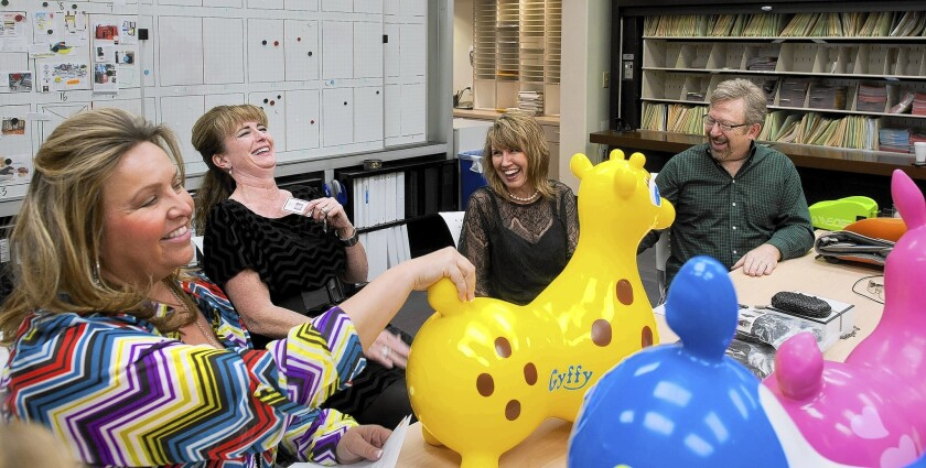 At SkyMall headquarters in Phoenix, Jennifer Williams, left, Liz Ford, Rita Jevicky and John Fischer talk about products in 2014. SkyMall filed for bankruptcy protection Thursday.