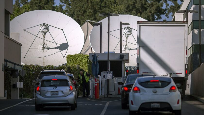 Satellite dishes are seen near a gate to Fox Studios in Century City.