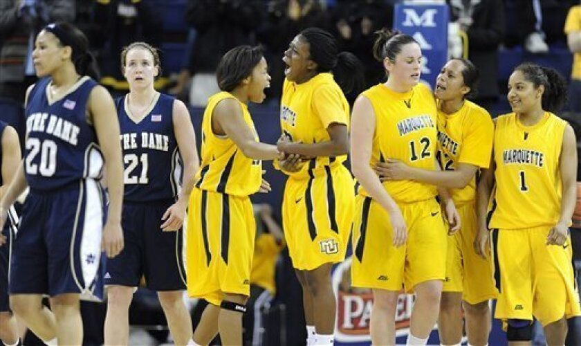 Marquette's Krystal Ellis, center left, and Tatiyiana McMorris, center right, celebrate near a trio of teammates in the closing seconds of an NCAA college basketball game, as Notre Dame's Ashley Barlow, left, and Natalie Novosel walk away, Tuesday, Jan. 13, 2009, in Milwaukee. Marquette won 75-65.