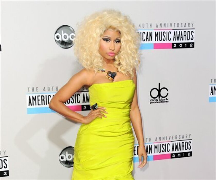 """FILE- In this Nov. 18, 2012 file photo, Nicki Minaj arrives at the 40th Anniversary American Music Awards, in Los Angeles. Despite having a big year in music, Nicki Minaj didn't receive any Grammy nominations. The 30-year-old had one of last year's biggest hits with the multiplatinum dance-pop anthem """"Starships."""" Her sophomore album, """"Pink Friday: Roman Reloaded,"""" has reached gold status and launched other hits on the rap and R&B charts. But Minaj was shunned out when the Grammys announced this year's nominees, though the animated performer earned three nominations last year, including best new artist and best rap album for her platinum debut, """"Pink Friday."""" (Photo by Jordan Strauss/Invision/AP, File)"""