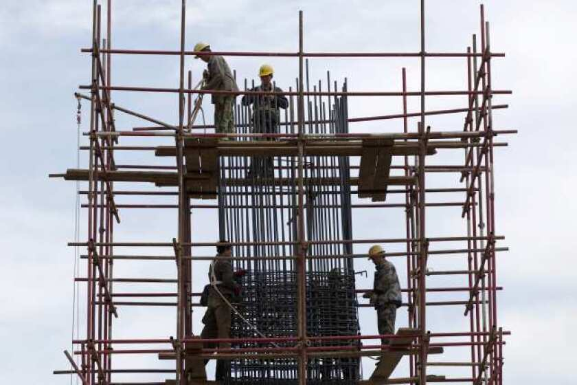 Workers stand on scaffolding at a road construction site in Beijing. Economic growth around the world, including in China, will continue, according to the IMF. But the environment remains fragile.