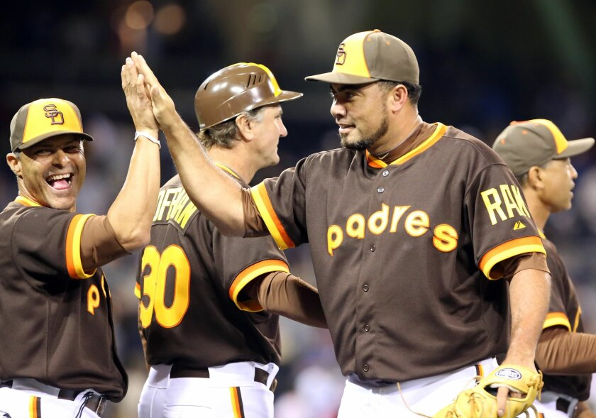 Padres pitcher Joaquin Benoit, second from right, celebrates with teammates and coaches after their 11-1 win over the Chicago Cubs in a baseball game Friday, May 23, 2014, in San Diego.